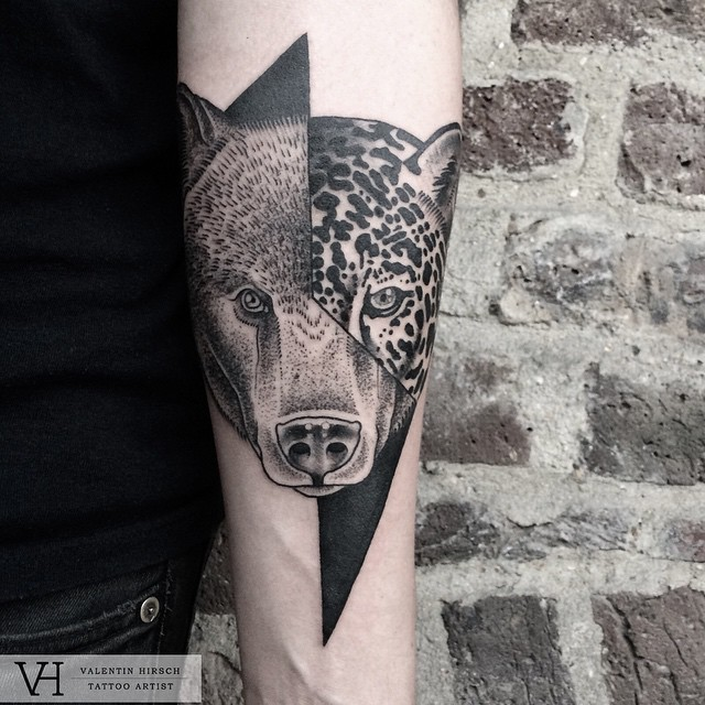 Engraving style black and white forearm tattoo of half bear half leopard