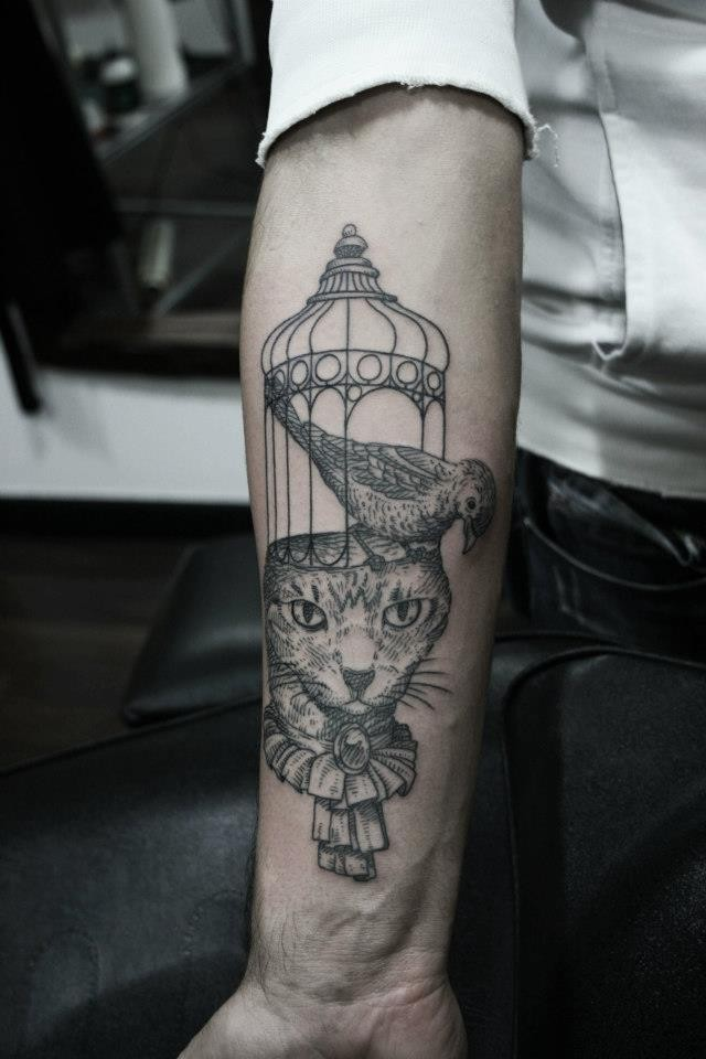 Engraving style black ink arm tattoo of cat head with bird and cage