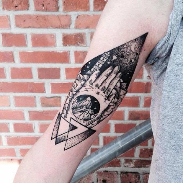 Engraving style black ink arm tattoo of human hands with lighthouse and night sky