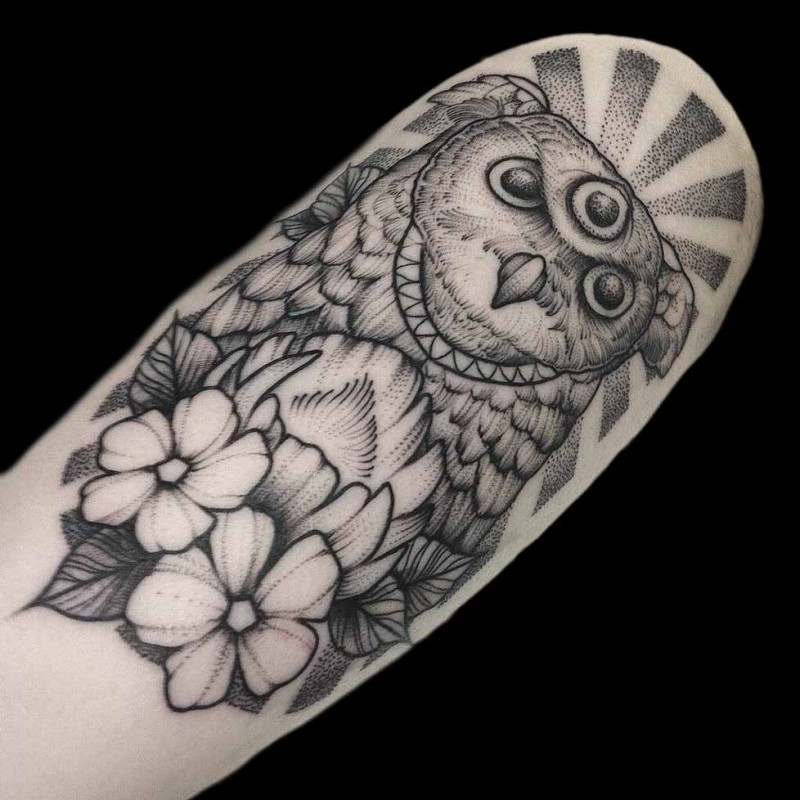 Engraving style black ink arm tattoo of fantasy owl with flowers