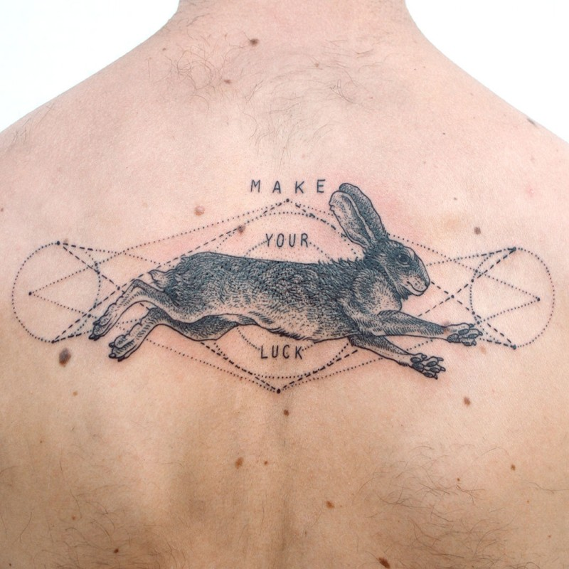 Engraving style black ink back tattoo of rabbit and lettering