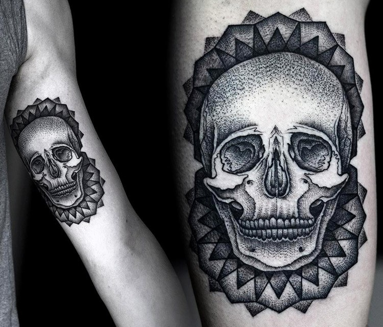 Engraving style black ink biceps tattoo of human skull with ornaments