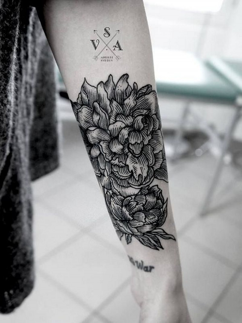 Engraving style black ink flower tattoo on forearm combined with lettering