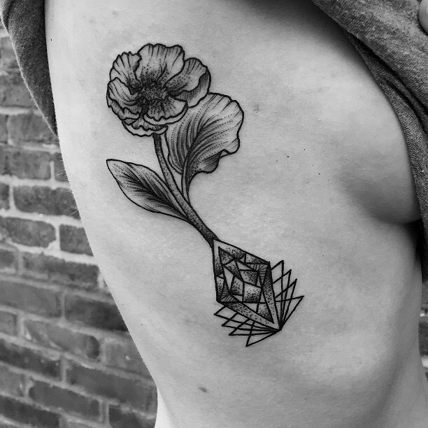 Engraving style black ink flower tattoo on side combined with geometrical figures