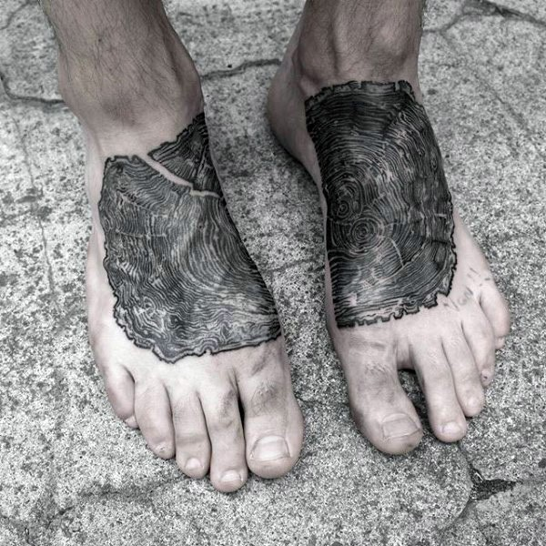 Engraving style black ink foot tattoo of tree branch