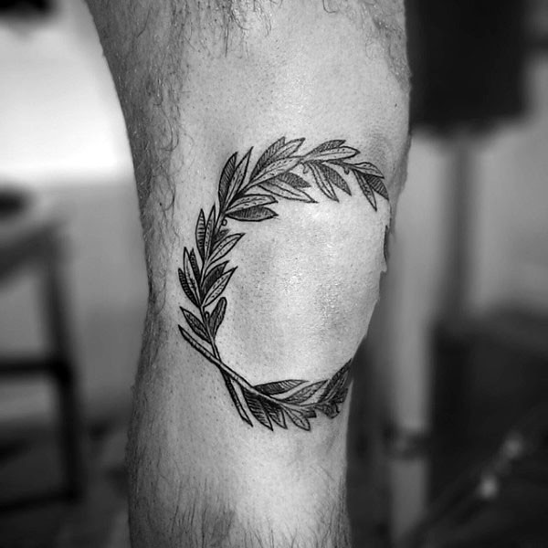 Engraving style black ink knee tattoo of leaves