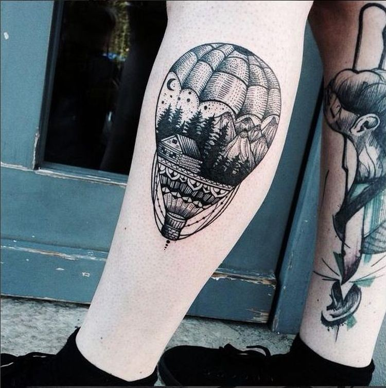 Engraving style black ink leg tattoo of large balloon stylized with forest house and mountains