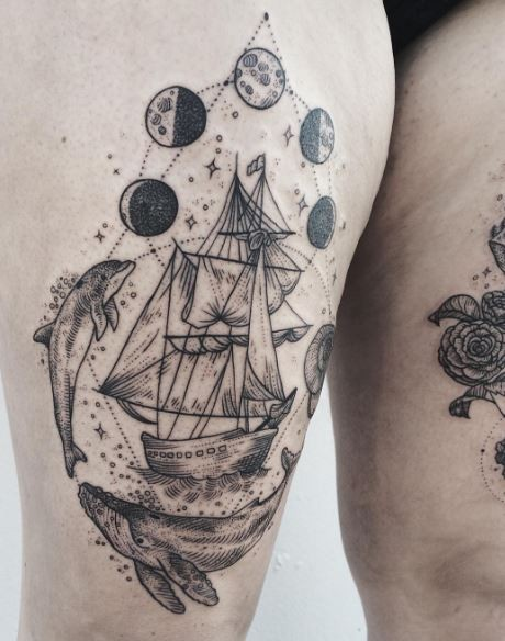 Engraving style black ink sailing ship tattoo on thigh with moon cycle and whales