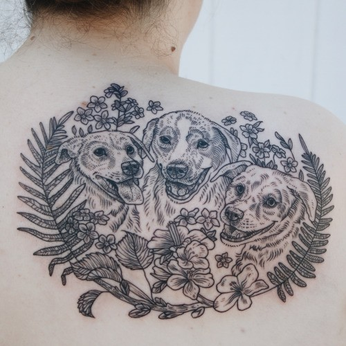 Engraving style black ink scapular tattoo of dogs family and wildflowers