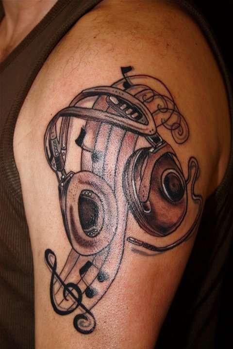 Engraving style black ink shoulder tattoo of headset and notes