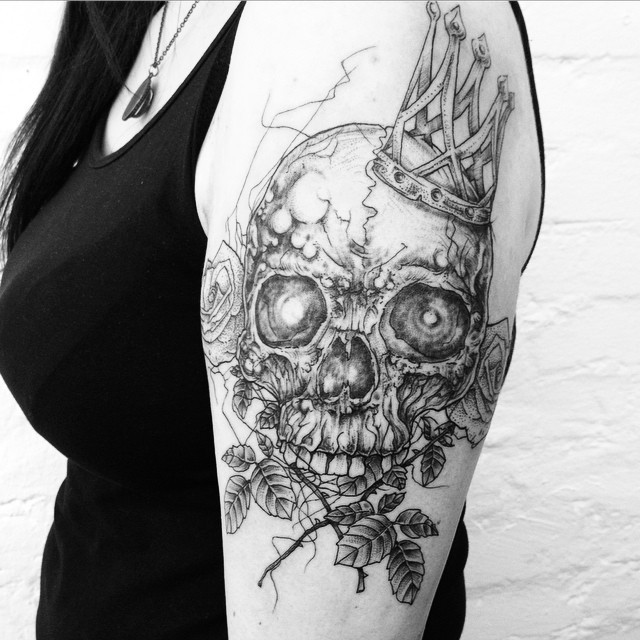 Engraving style black ink shoulder tattoo fo human skull with crown and roses