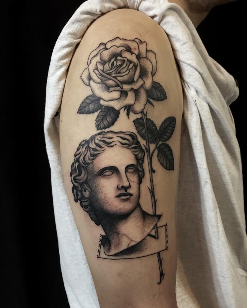 Engraving style black ink shoulder tattoo of big rose with vintage statue