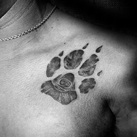 Engraving style black ink shoulder tattoo of paw print stylized with wolf face