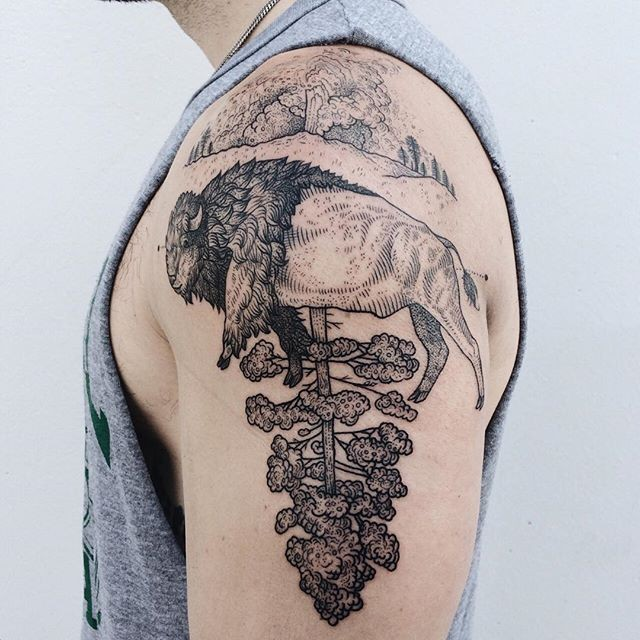 Engraving style black ink shoulder tattoo of bull with tree