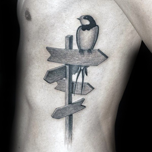 Engraving style black ink side tattoo of bird on road sign