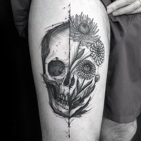 Engraving style black ink thigh tattoo of human skull with flowers