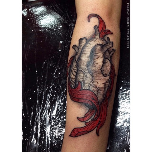 Engraving style colored arm tattoo of human heart with flames