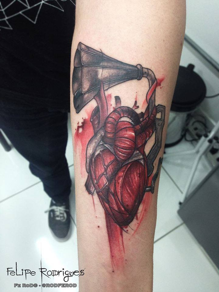 Engraving style colored forearm tattoo of human heart with gramophone