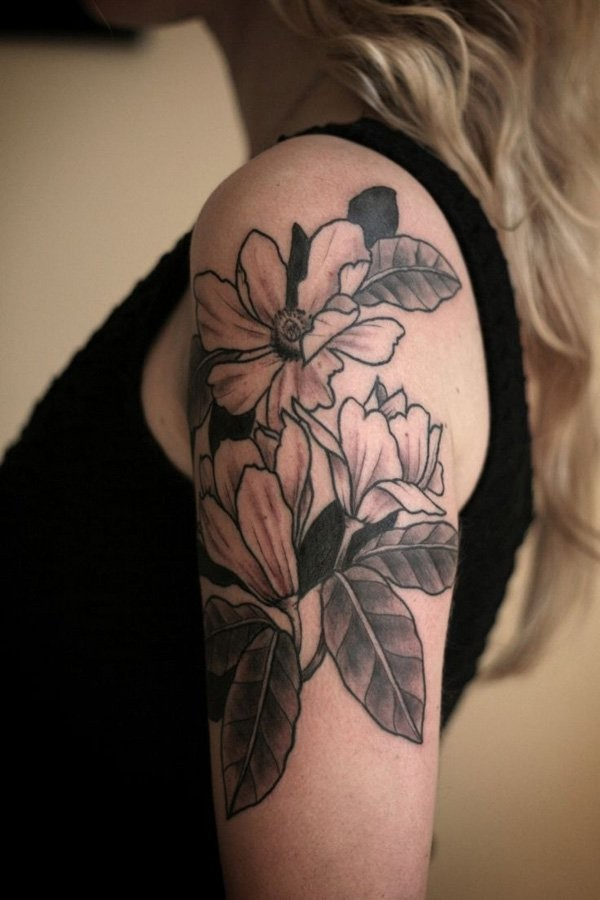 Engraving style colored shoulder tattoo of flowers with leaves