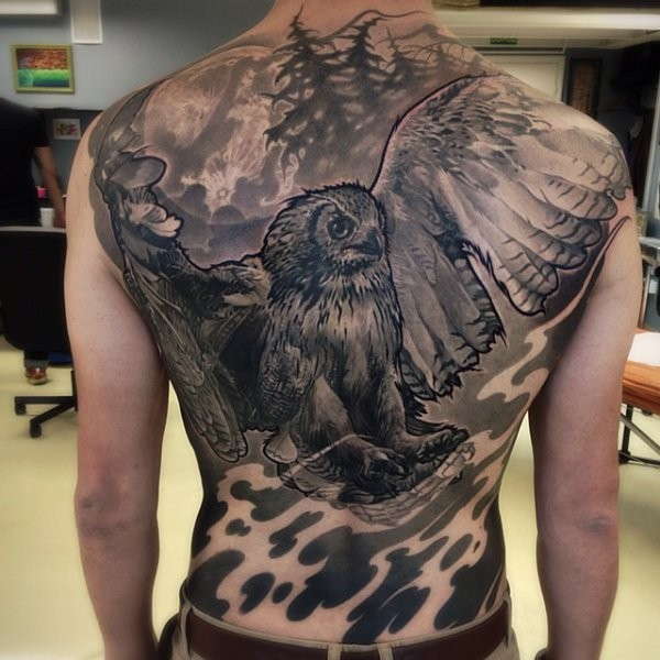 Enormous black ink whole back tattoo of detailed owl in dark forest