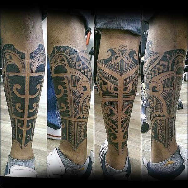 Ethnic tribal style dark black ink leg armor tattoo