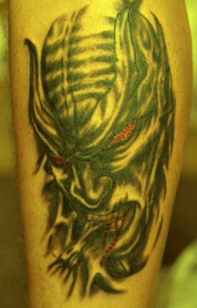 Tatuaggio spaventoso sulla gamba la testa del demone con gli occhi rossi