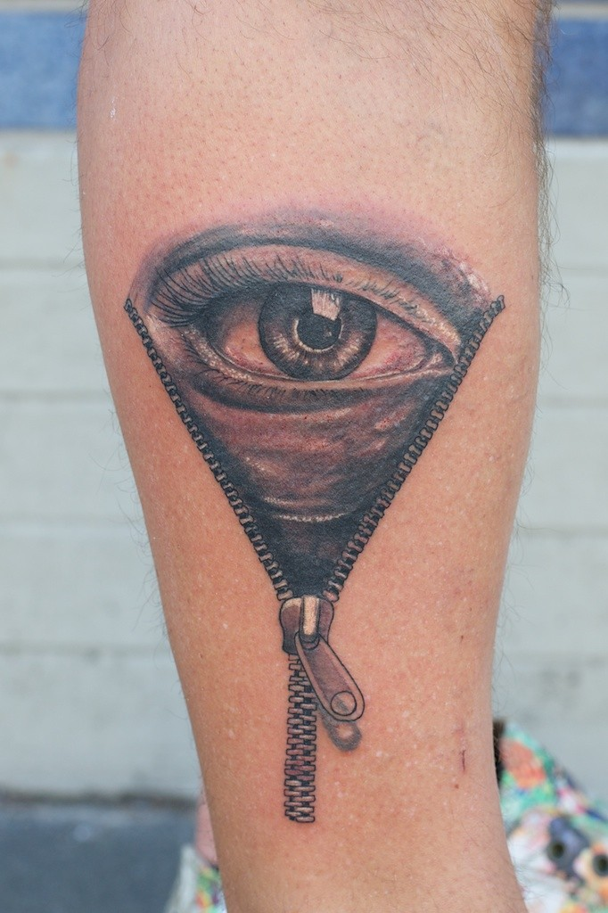Tatuaggio colorato sul braccio l&quotocchio grande tra la zip