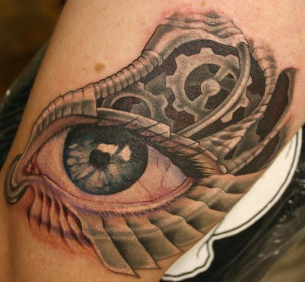 Tatuaggio colorato sulla gamba l&quotocchio grande in stile meccanico