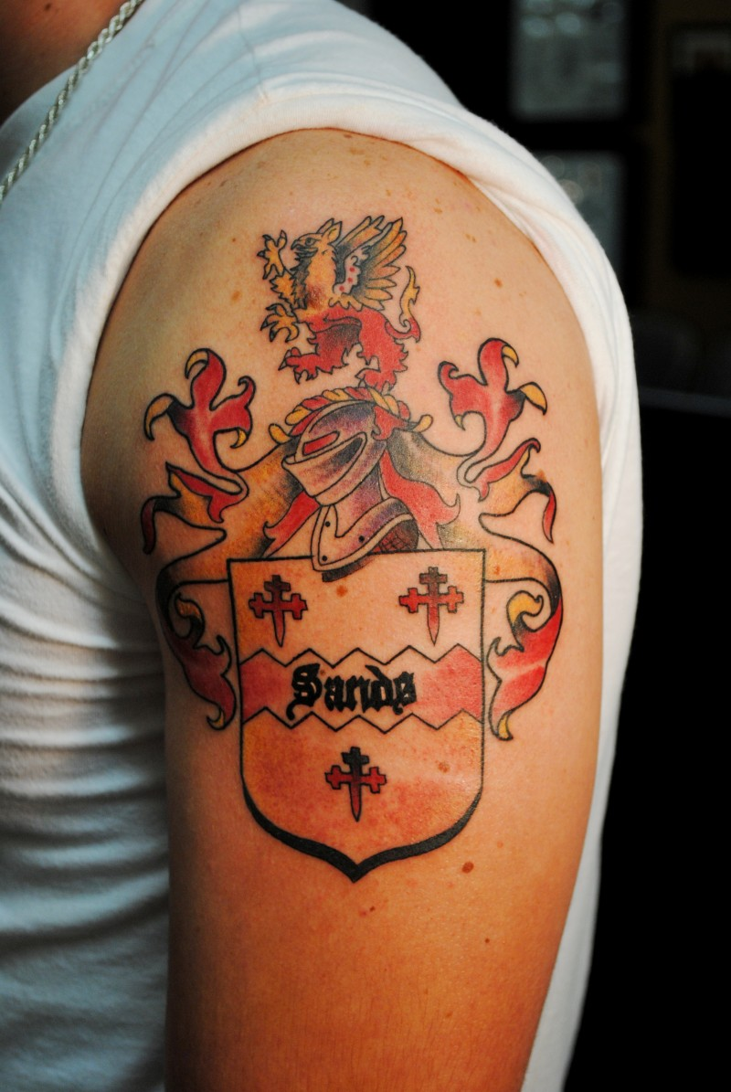 Family crest with a knight tattoo on shoulder for Family motto tattoos