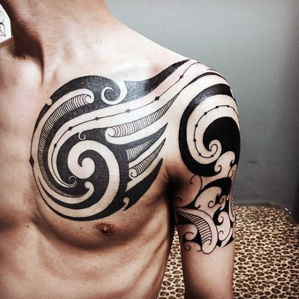 Fantastic black and white tribal tattoo on shoulder and chest