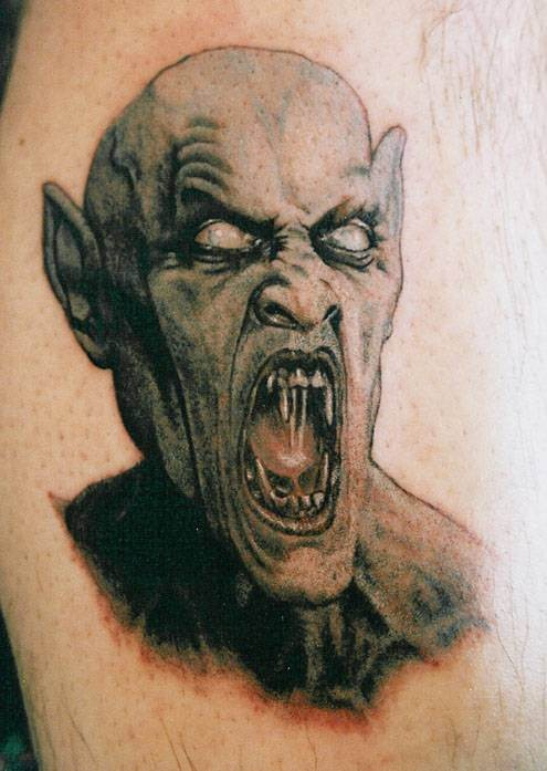 Fantastic designed and painted creepy vampire monster tattoo on leg