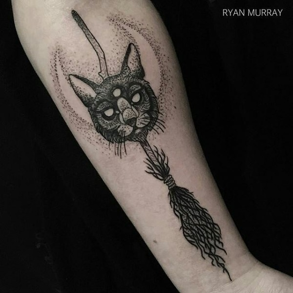 Fantastic looking black ink arm tattoo of cat mask with broom