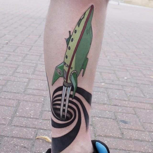 Fantasy cartoon like colored space ship tattoo on leg with hypnotic symbol