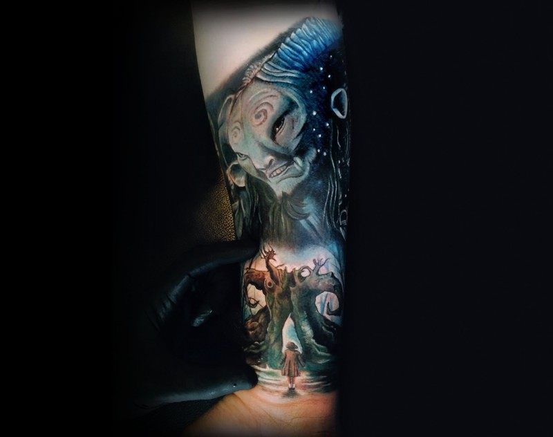 Fantasy style colored forearm tattoo of devil with girl
