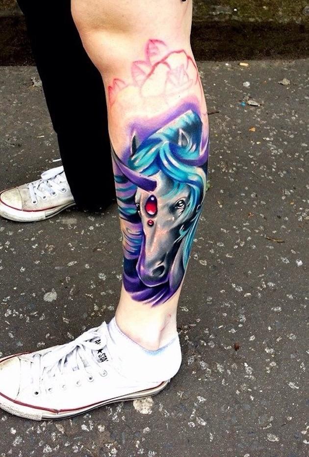 Fantasy style colored little unicorn head tattoo on leg