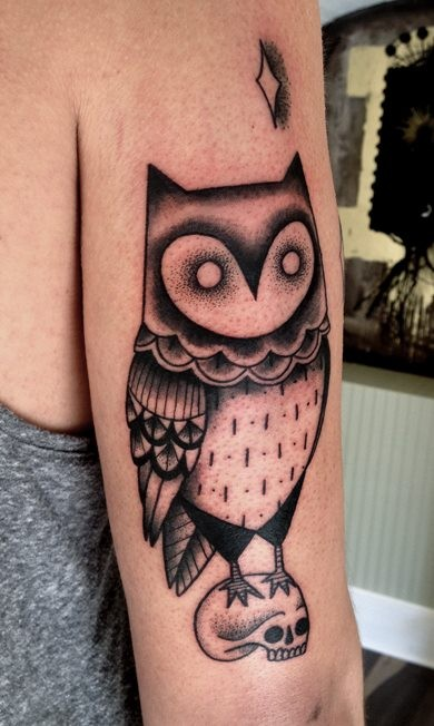 Fantasy style designed black ink owl tattoo on arm combined with star and skull