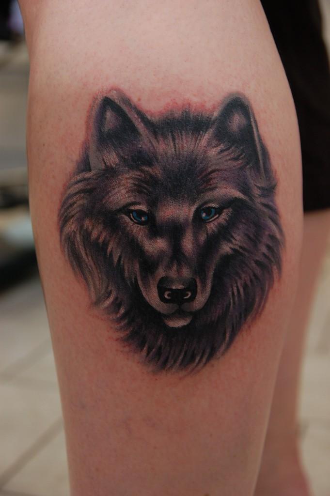 Feminine wolf face tattoo on leg
