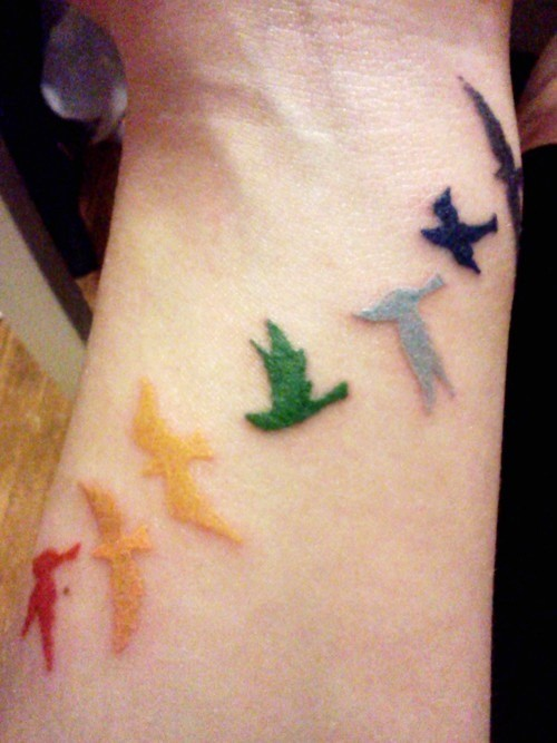 Flock of colored birds tattoo