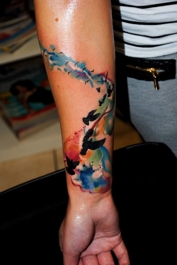 Flock of flying dark black birds tattoo on forearm with watercolor stains