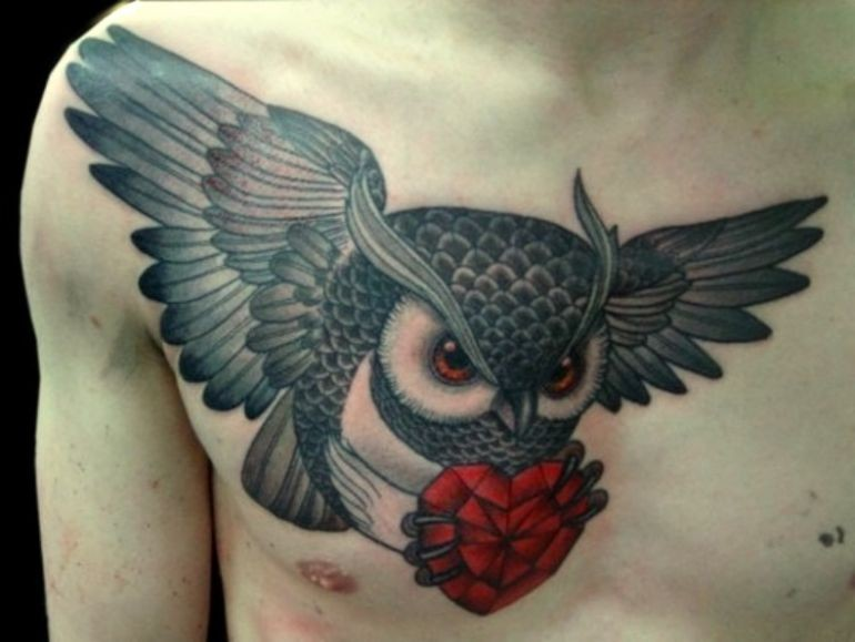 Flying owl with a red heart in its claws tattoo on chest