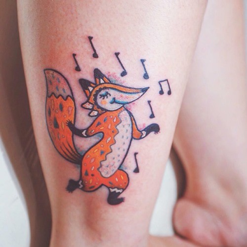 Funny cartoon dancing fox and music notes colored tattoo on ankle