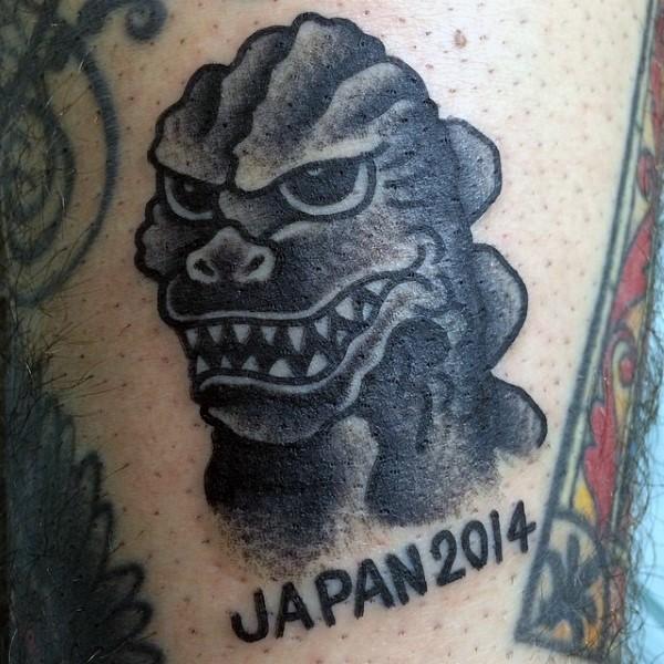 Funny cartoon like black ink Godzilla with lettering tattoo on arm