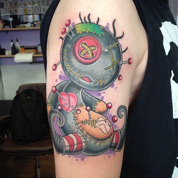 Funny cartoon like colored shoulder tattoo of corrupted voodoo doll