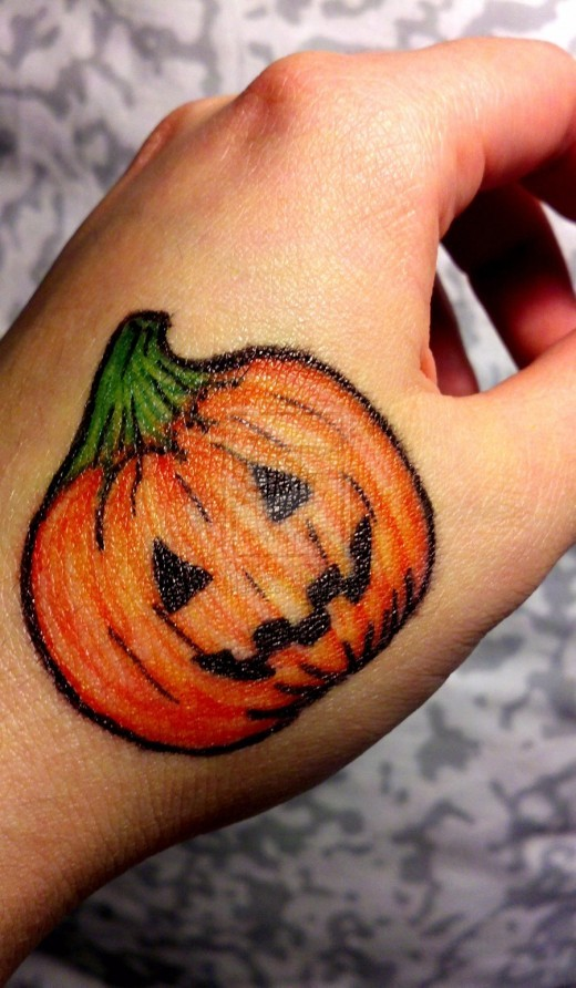 Funny colored halloween pumpkin tattoo on hand for Tattoos of pumpkins