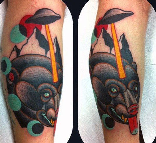 Funny combined multicolored bear with alien ship tattoo on leg