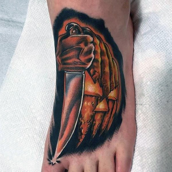Funny designed maniac pumpkin with knife tattoo on foot