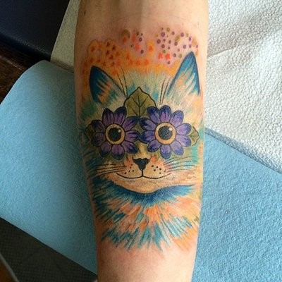 Funny fairy tale cat with floral eyes bright colored detailed forearm tattoo
