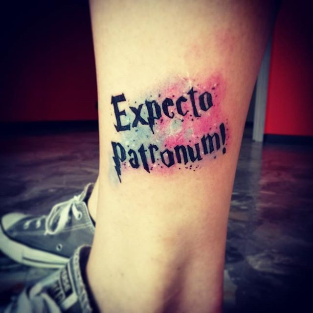 "Funny Harry Potter style colored ankle tattoo of &quotExpecto patronum"" lettering"