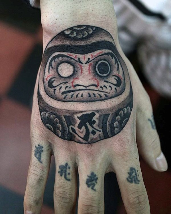 Funny illustrative style hand tattoo of daruma doll with lettering