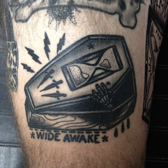 Funny little black ink coffin with sand clock, lettering and skeleton hand tattoo on thigh